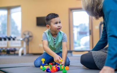 Young boy building with toys with occupational therapist