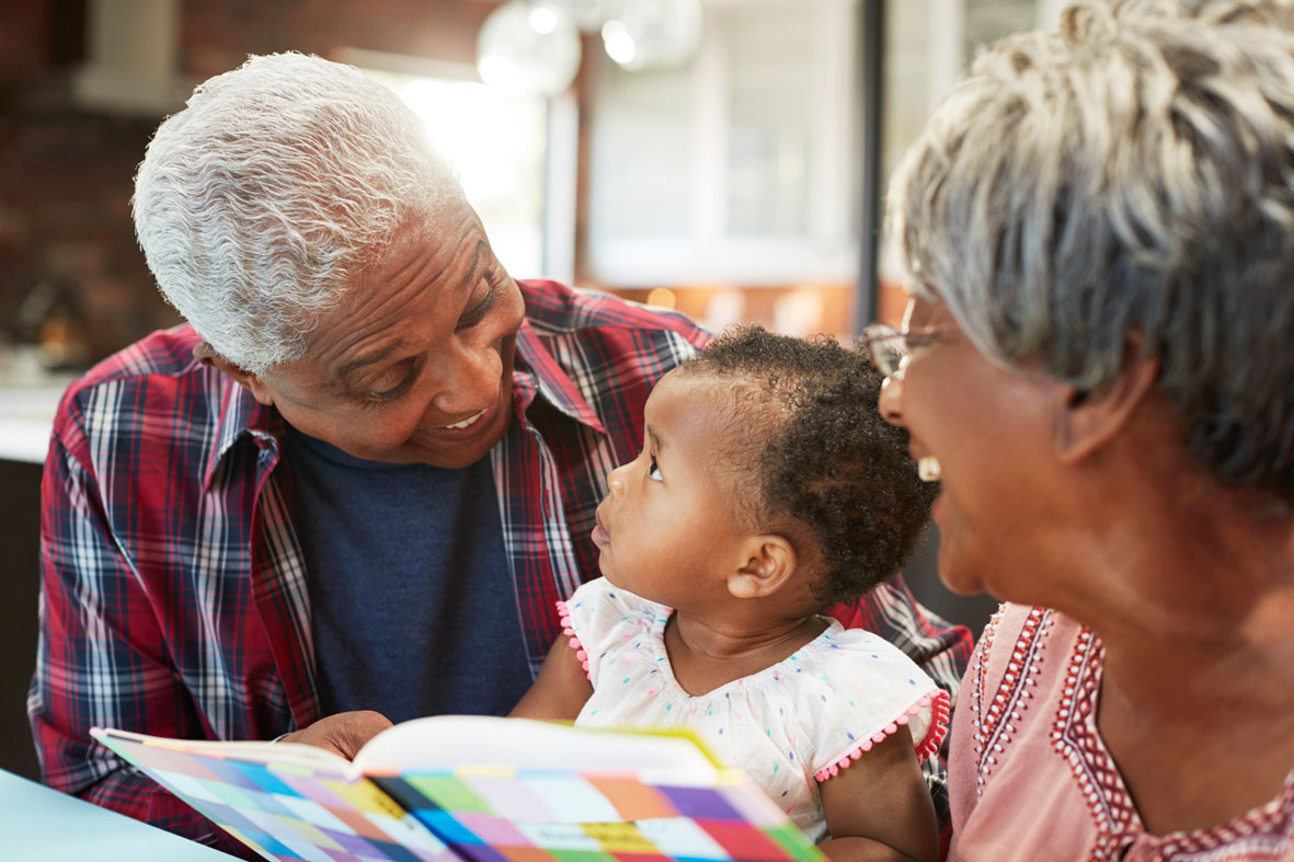 Grandparents reading to infant