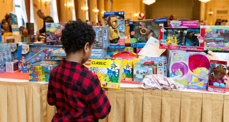 Young boy looking at a table full of toys