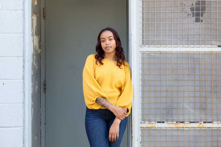Kahleen, wearing yellow sweater, standing in doorway