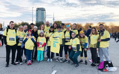 "19 people standing in parking lot wearing yellow ""Stand Up for Kids"" team t-shirts, preparing for the Scotiabank Toronto Waterfront 5K"