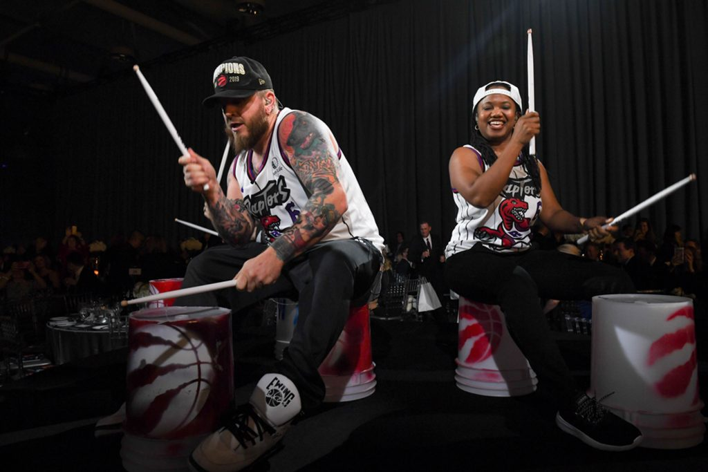 One male and one female drummer from The 6ix Stix, drumming on buckets with Raptors logos on them, holding drumsticks in the air