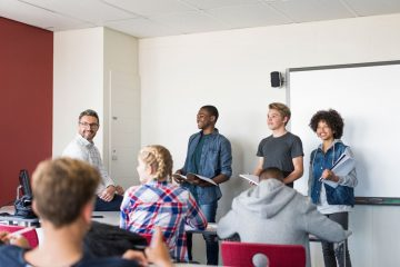 Multi-ethnic teenage friends giving presentation in classroom. Smiling mature male professor is sitting amidst students. They are wearing casuals in high school building.