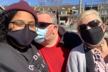BRITTANY standing with her foster parents, all wearing masks. Her foster dad is kissing her cheek.