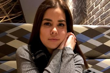 GABRIELA with long, dark hair sits at a restaurant table wearing a grey shirt, her elbows on the table with her hands clasped at the side of her face.